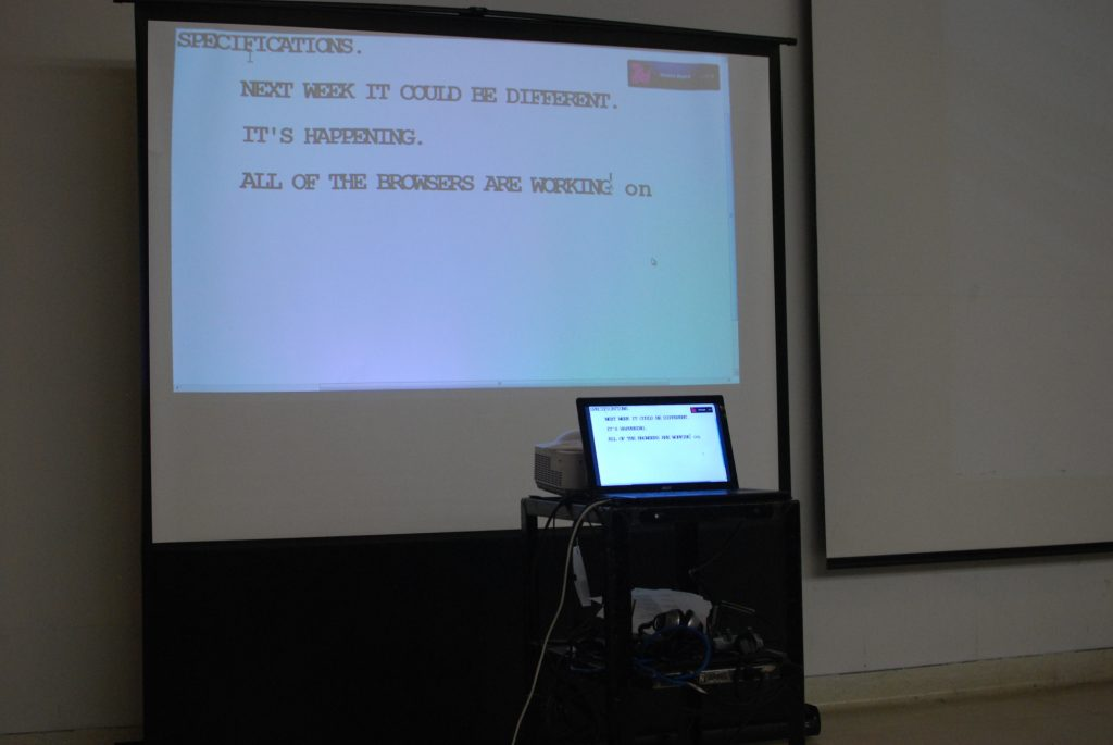 """A projector shows the text of a presentation at Accessibility Camp Toronto for the hard of hearing. Text reads: """"Next week it could be different. It's working. All of the browsers are working...[on becoming accessible]."""""""