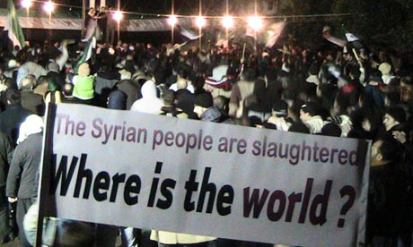 "Syrian protesters with a sign reading ""The Syrian people are slaughtered; where is the world?"""