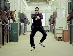 """A still image from PSI's music video for """"Gangnam Style"""" showing him dancing in a horse stable."""